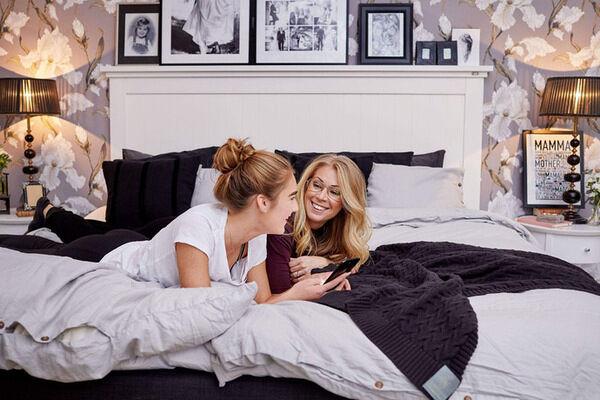 Therese och dottern ligger på sängen.