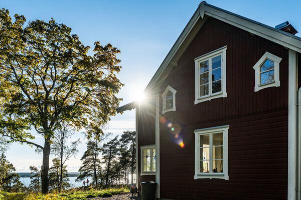Rött hus med sol och träd